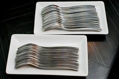 Beaucoup de fourchettes sur un plat blanc Photo stock