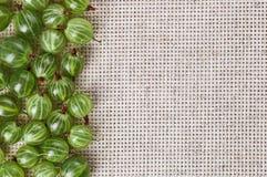 Beaucoup de fruits de groseille à maquereau sur le tissu de table de toile gris Image stock