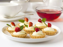 Beaucoup de gâteaux ou de mini tarte avec les fruits frais, la crème fouettée et les menthes Photos libres de droits