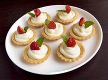 Beaucoup de gâteaux, petits gâteaux avec des fruits frais (fraises), ont fouetté la crème et des menthes Images stock