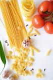Beaucoup de genres de pâtes et de légumes sur le fond blanc Image stock