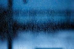 Beaucoup de gouttelettes sur un fond transparent de bleu de fenêtre Photographie stock libre de droits