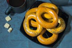 Beaucoup de grands bagels d'un plat noir et d'un sucre sur une nappe bleue Image stock