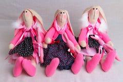 Beaucoup de lapins de jouet dans des robes, Pâques Photos stock