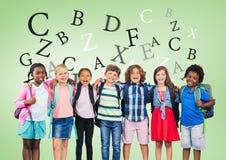 Beaucoup de lettres autour d'école multiculturelle badine devant le fond vert Photo stock