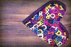 Beaucoup de lettres colorées dans la forme en bois de coeur Photo stock