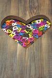 Beaucoup de lettres colorées dans la forme en bois de coeur Photos libres de droits