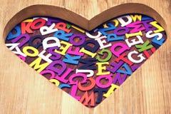 Beaucoup de lettres colorées dans la forme en bois de coeur Photos stock