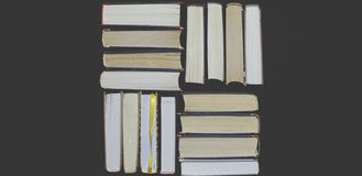 Beaucoup de livres ouverts épais multicolores se tiennent sur un fond foncé Sur les livres sont les vieux verres ronds et un carn photographie stock libre de droits