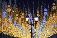 Beaucoup de lumières brûlantes lumineuses bleues et lanternes jaunes accrochant sur le plan rapproché noir de fond de ciel noctur images libres de droits