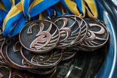 Beaucoup de médailles de bronze avec les rubans de cuivre et les rubans bleus jaunes sur un plateau argenté, récompenses de champ photos stock