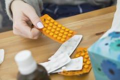 Beaucoup de médecines sur la table de nuit dans la chambre à coucher Femme prenant des pillules Images libres de droits
