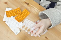 Beaucoup de médecines sur la table de nuit dans la chambre à coucher Femme prenant une médecine Photos libres de droits