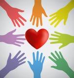 Beaucoup de mains colorées entourant un coeur rouge Photo stock