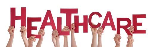 Beaucoup de mains de personnes tenant des soins de santé rouges de Word Image stock