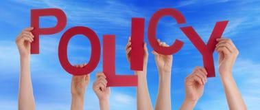 Beaucoup de mains de personnes tenant le ciel bleu de politique rouge de Word Photos stock