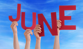 Beaucoup de mains de personnes tenant le ciel bleu rouge de Word juin Photos libres de droits