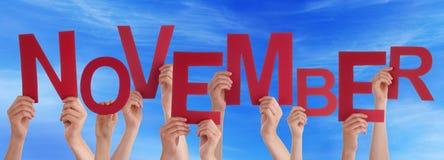 Beaucoup de mains de personnes tenant le ciel bleu rouge de Word novembre Images libres de droits