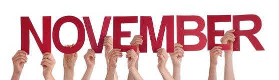 Beaucoup de mains de personnes tenant Word droit rouge novembre Image stock