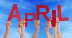 Beaucoup de mains de personnes tenant Word rouge April Blue Sky Image stock