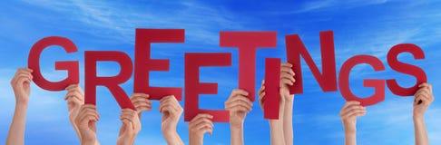 Beaucoup de mains de personnes tiennent le ciel bleu de salutations rouges de Word Image libre de droits