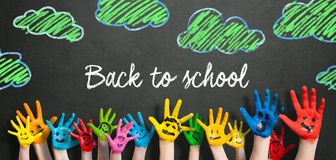 Beaucoup de mains peintes d'enfants avec des smiley et le ` de message de nouveau au ` d'école photographie stock libre de droits