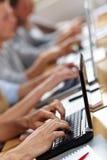 Beaucoup de mains sur des ordinateurs portatifs Images stock