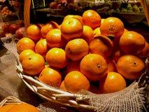 Beaucoup de mandarines oranges fraîches se situent dans un panier fait de vignes sur une fenêtre de magasin images stock