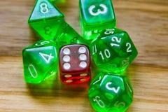Beaucoup de matrices jouantes vertes translucides sur un fond en bois W photo libre de droits