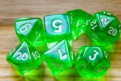Beaucoup de matrices jouantes vertes translucides sur un fond en bois W photographie stock libre de droits