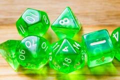Beaucoup de matrices jouantes vertes translucides sur un fond en bois W image stock