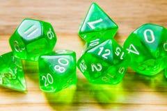 Beaucoup de matrices jouantes vertes translucides sur un fond en bois W image libre de droits