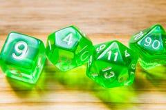 Beaucoup de matrices jouantes vertes translucides sur un fond en bois W images libres de droits