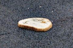 Beaucoup de pain se trouve sur l'asphalte, pain corrompu, faim photographie stock libre de droits