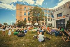 Beaucoup de personnes détendant avec des familles sur la pelouse pendant le festival extérieur populaire Photographie stock