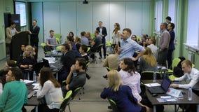 Beaucoup de personnes dans la chambre se reposant ensemble aux tables et participant en cours de teambuilding Hommes et femmes banque de vidéos