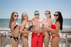 Beaucoup de personnes heureuses et gaies dans des costumes de natation sur un fond lumineux de mer Portrait d'été des personnes a Image stock