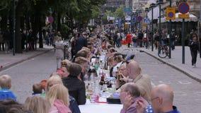 Beaucoup de personnes mangeant et buvant à la même table sur la rue Laps de temps banque de vidéos