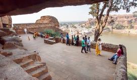 Beaucoup de personnes marchant autour des temples indous du 6ème siècle de caverne près d'un lac de Karnataka antique Photographie stock libre de droits