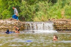 Beaucoup de personnes nageant au petit déversoir irriguent Photographie stock libre de droits