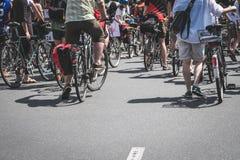 Beaucoup de personnes sur des bicyclettes dessus sur la rue Images stock
