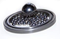 Beaucoup de petites boules inoxydables reflétant dans une grande boule inoxydable dans un roulement à billes mince photo libre de droits