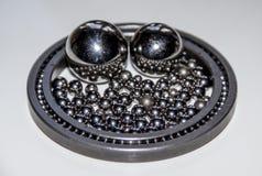 Beaucoup de petites boules inoxydables reflétant dans une paire de grandes boules inoxydables dans un roulement à billes mince av image stock