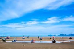 Beaucoup de petits bateaux de pêche sur le sable échouent pendant la marée basse avec le ciel bleu nuageux Image stock