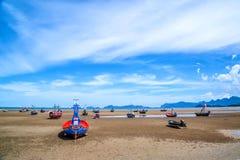 Beaucoup de petits bateaux de pêche sur le sable échouent pendant la marée basse avec le ciel bleu nuageux Images stock