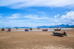 Beaucoup de petits bateaux de pêche sur le sable échouent pendant la marée basse avec le ciel bleu nuageux Image libre de droits