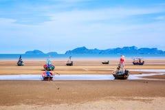 Beaucoup de petits bateaux de pêche sur le sable échouent pendant la marée basse avec le ciel bleu nuageux Photographie stock
