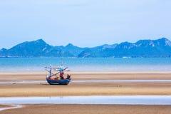 Beaucoup de petits bateaux de pêche sur le sable échouent pendant la marée basse avec le ciel bleu nuageux Photo stock