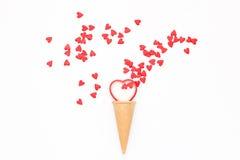 Beaucoup de petits coeurs rouges volant hors du cône de gaufre sur le fond blanc Photographie stock libre de droits