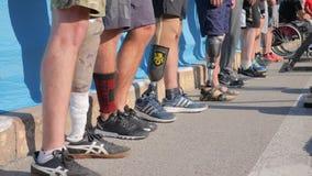 Beaucoup de pieds prosthétiques masculins se tiennent dans la rangée près de l'un l'autre sur la route goudronnée banque de vidéos
